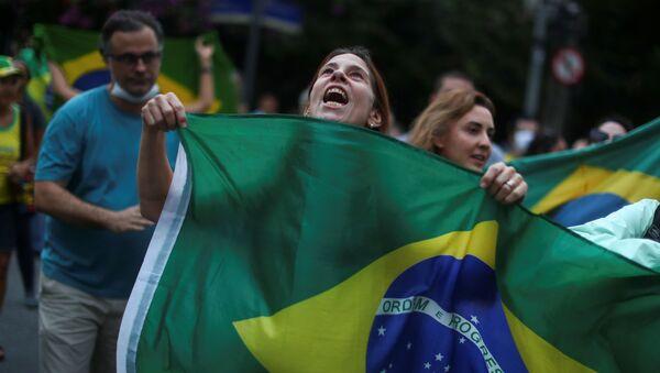 Una mujer sostiene la bandera de Brasil en una manifestación en Río de Janeiro - Sputnik Mundo