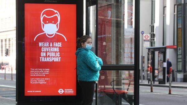 Una chica con mascarilla en una parada de autobús en Londres, Reino Unido - Sputnik Mundo