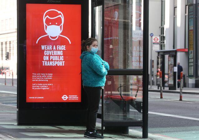 Una chica con mascarilla en una parada de autobús en Londres, Reino Unido