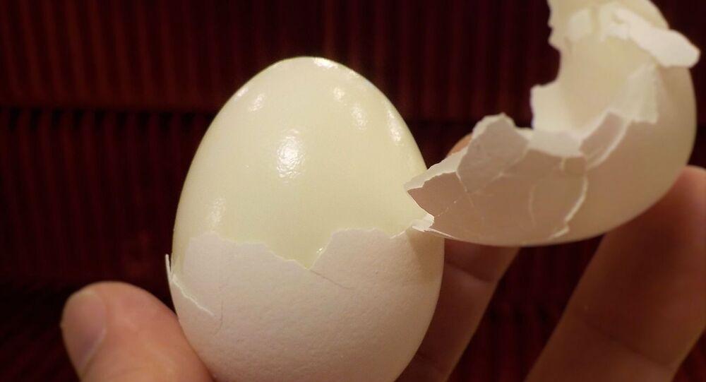 Persona pelando un huevo