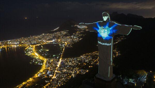 Estatua de Cristo Redentor con iluminación en forma de máscara y con una inscripción en portugués que reza 'La máscara salva' en Río de Janeiro, Brasil. - Sputnik Mundo