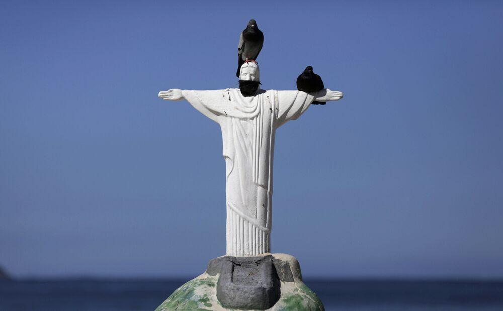 Una escultura de arena del Cristo Redentor con una máscara protectora en la playa de Copacabana de Río de Janeiro, Brasil.