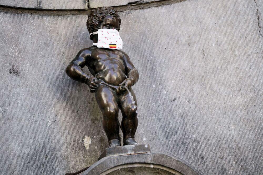 La famosa estatua de bronce del Manneken Pis, en Bruselas, con una mascarilla.