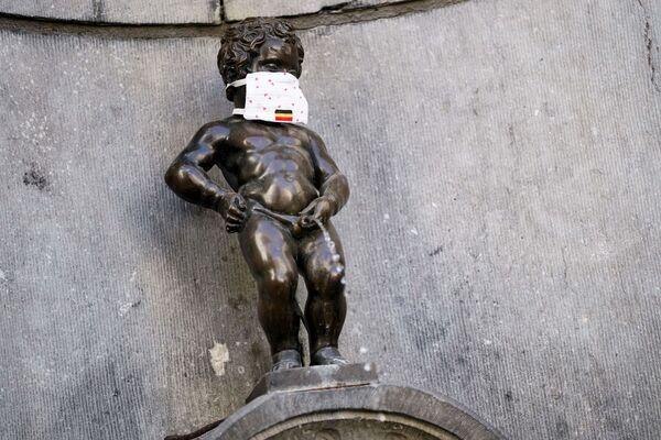 La famosa estatua de bronce del Manneken Pis, en Bruselas, con una mascarilla. - Sputnik Mundo
