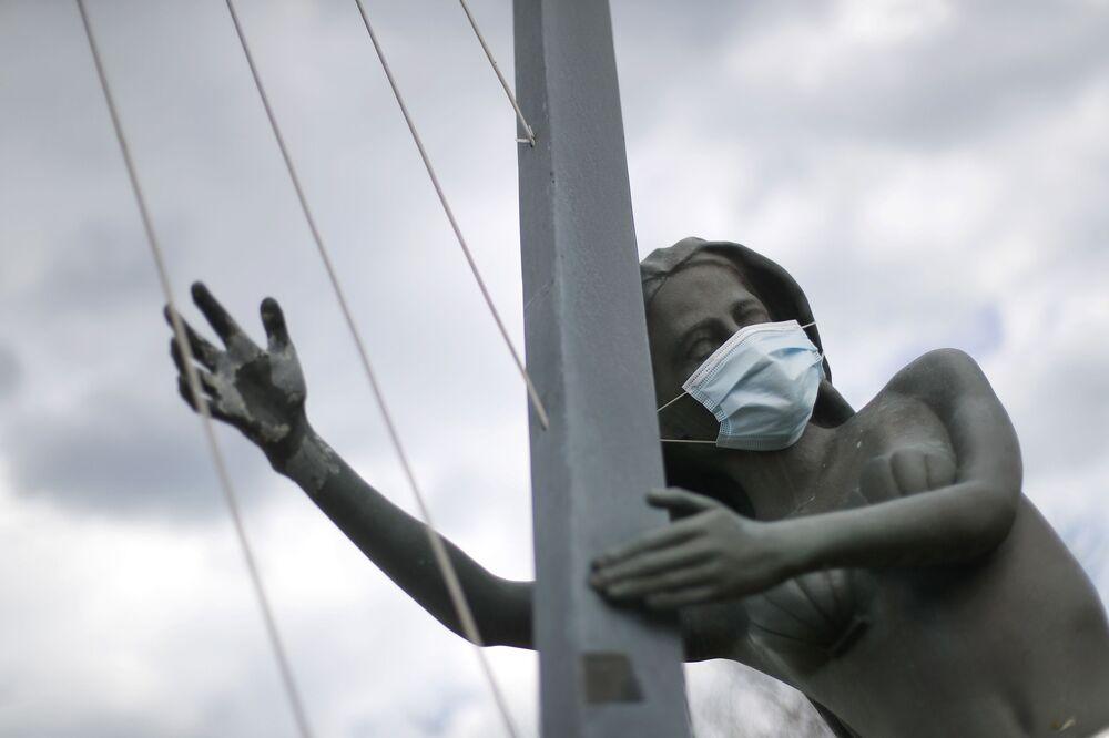Estatua de una sirena con una mascarilla protectora en St. Clair Shores, Michigan, EEUU.