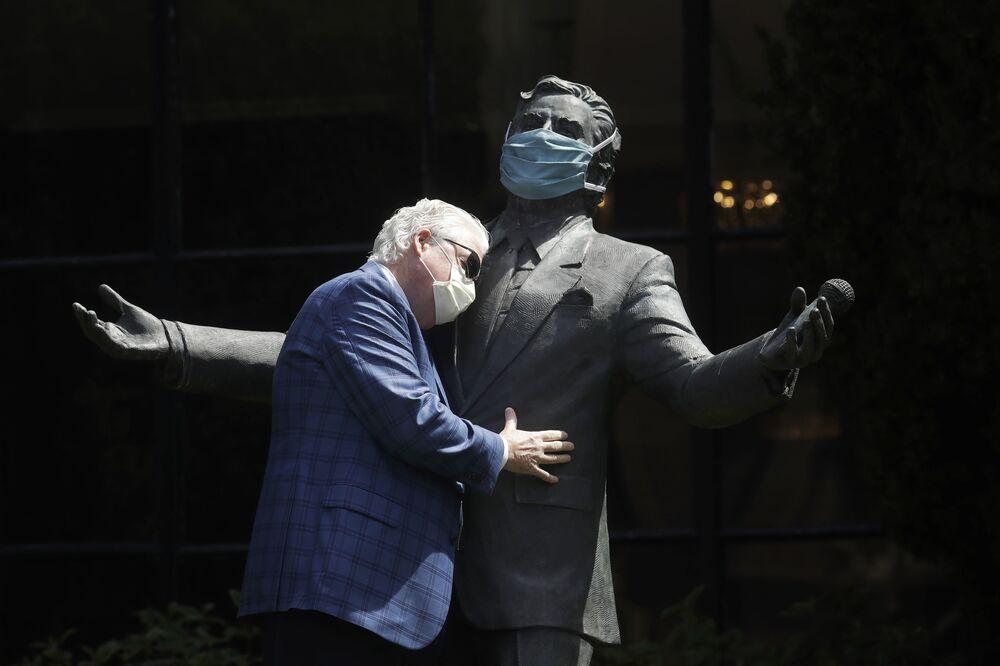 Paul Tormey, vicepresidente de Fairmont Hotels, abraza la estatua del cantante Tony Bennett en el Hotel Fairmont San Francisco de la ciudad del mismo nombre, en EEUU.