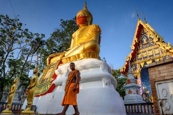 Una estatua gigante de Buda con una mascarilla en un templo de la provincia de Pathum Thani, en Tailandia.  - Sputnik Mundo
