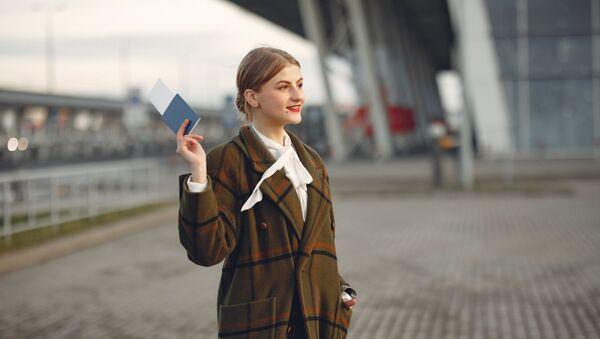Una joven con un pasaporte en la mano - Sputnik Mundo