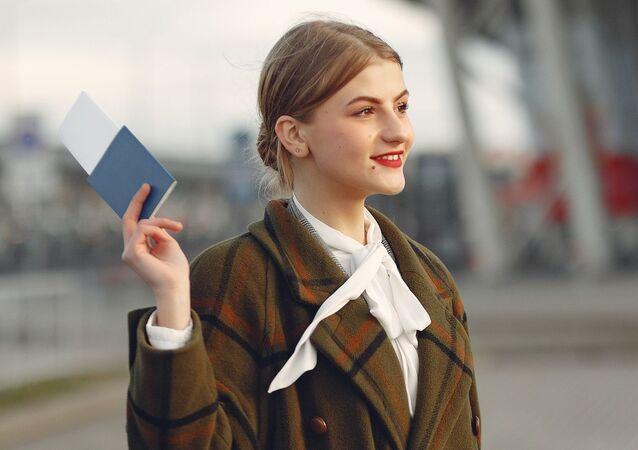 Una joven con un pasaporte en la mano