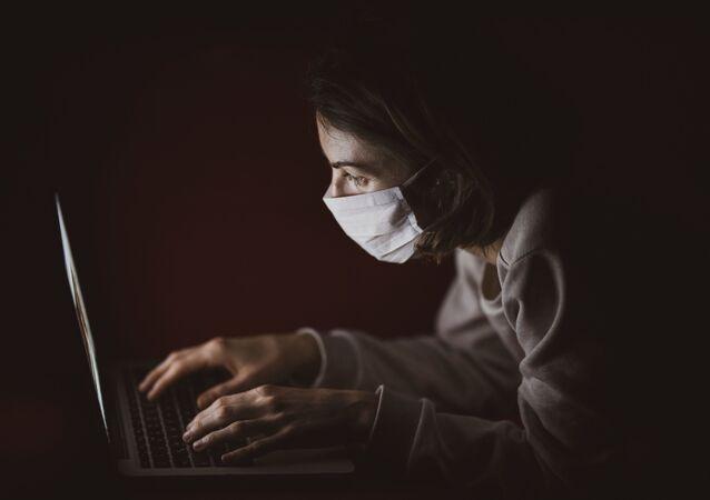 Una persona con mascarilla mirando la pantalla