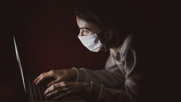 Una persona con mascarilla mirando la pantalla - Sputnik Mundo