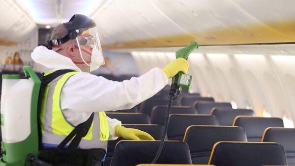 Un hombre desinfecta el interior de un avión de Ryanair - Sputnik Mundo