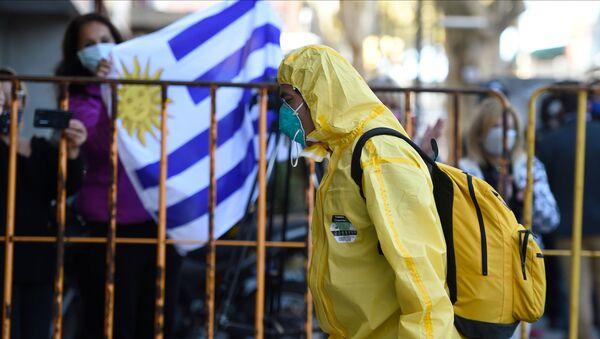 Un hombre con un traje de protección en Montevideo, Uruguay - Sputnik Mundo