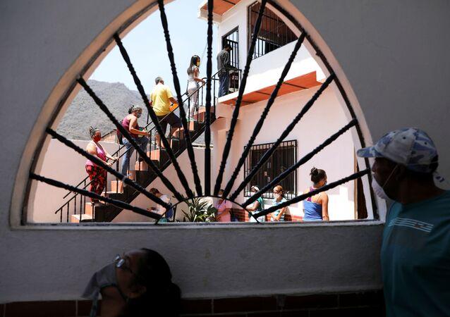 Venezolanos hacen cola para recibir alimentos en una favela en Caracas