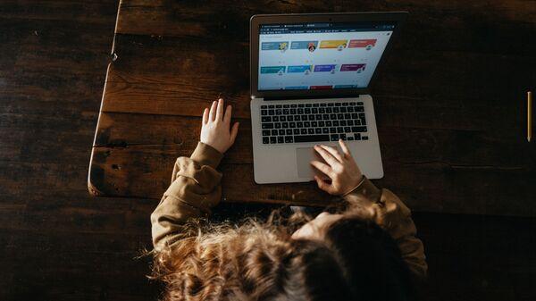Una niña con ordenador (imagen referencial) - Sputnik Mundo