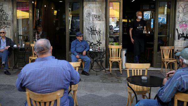 Un camarero sirve a los clientes de una cafetería el día que los restaurantes vuelven a abrir en Atenas tras el 'lockdown' por el COVID-19 - Sputnik Mundo