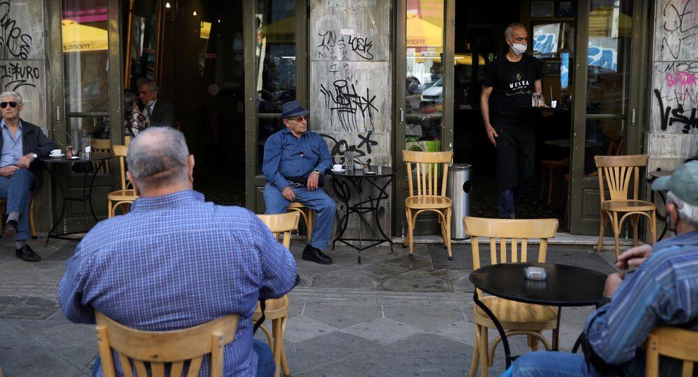 Un camarero sirve a los clientes de una cafetería el día que los restaurantes vuelven a abrir en Atenas tras el 'lockdown' por el COVID-19