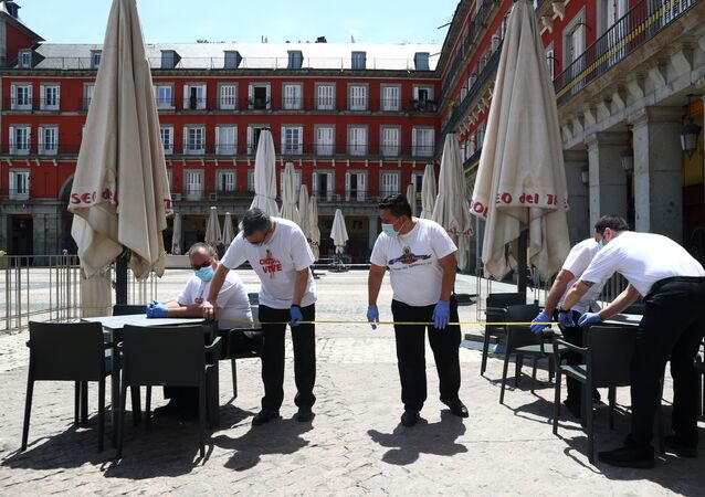 Trabajadores midiendo la distancia entre dos mesas en una terraza de la Plaza Mayor (Madrid)