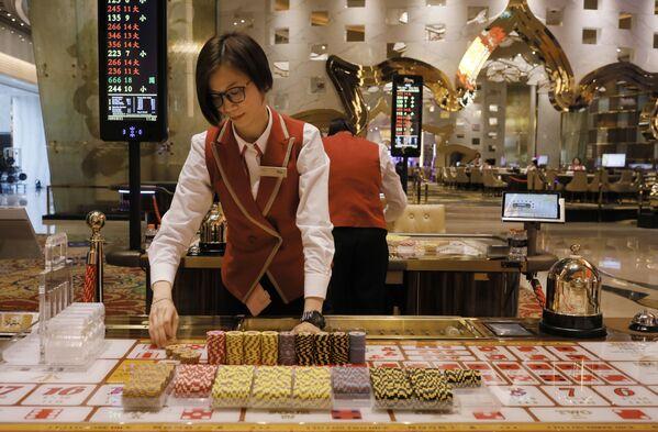 A croupier works at a gaming table at MGM Cotai Resort in Macau - Sputnik Mundo