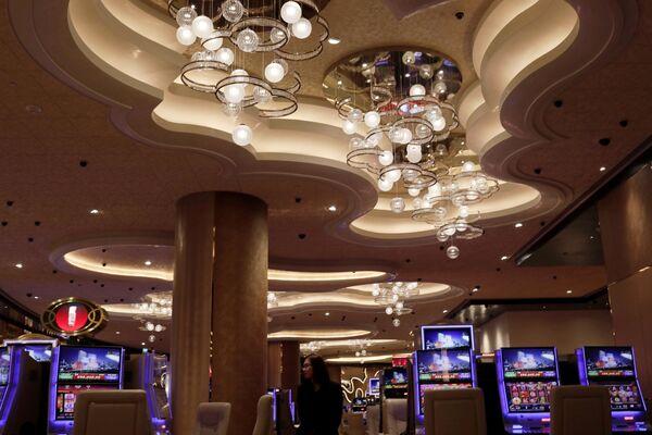 A woman walks past some slot machines at MGM Cotai Resort in Macau - Sputnik Mundo