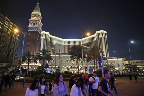 People walk across a road in front of the Venetian Macao casino resorts in Macau - Sputnik Mundo