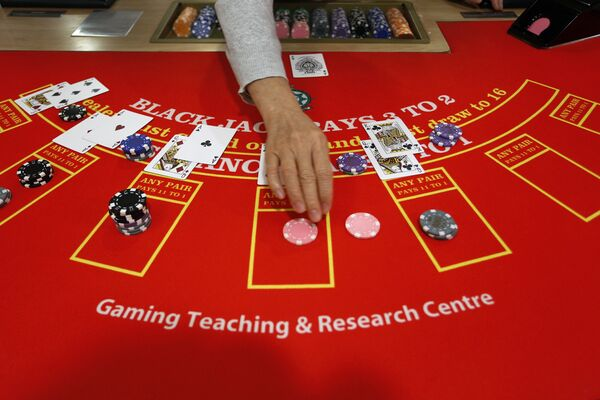A gambling school student practices on a table in Macau, China - Sputnik Mundo