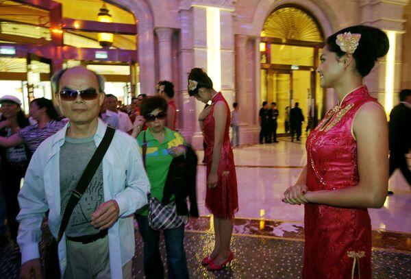 Mainland Chinese visitors walk past attendants at the Galaxy Macau in Macau.  - Sputnik Mundo