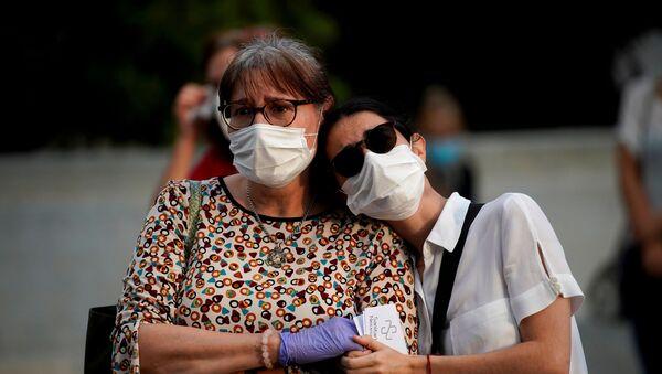 Dos mujeres con mascarillas durante brote de coronavirus en España - Sputnik Mundo