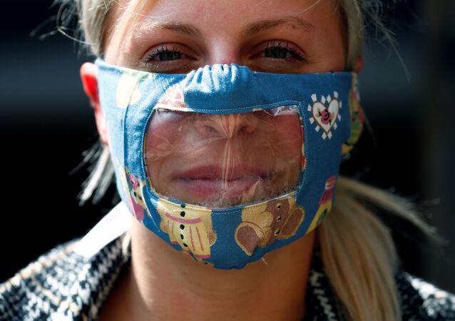 Una mujer con mascarilla transparente