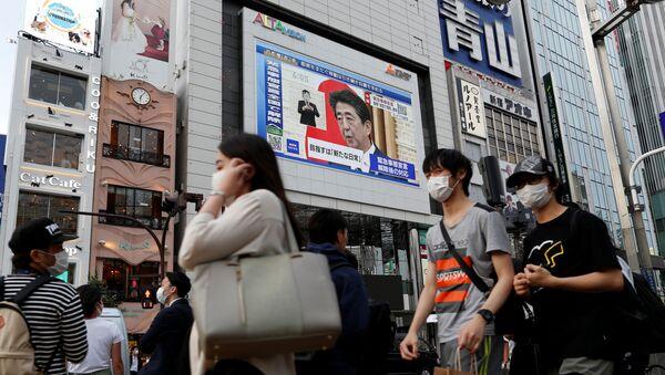 La imagen del primer ministro japonés Shinzo Abe en una pantalla en Tokio - Sputnik Mundo
