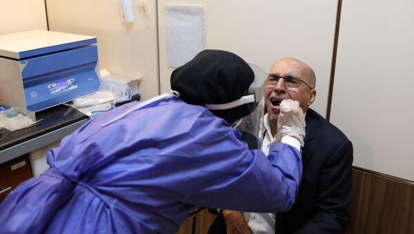 Un paciente haciendo un test por coronavirus en Irán - Sputnik Mundo