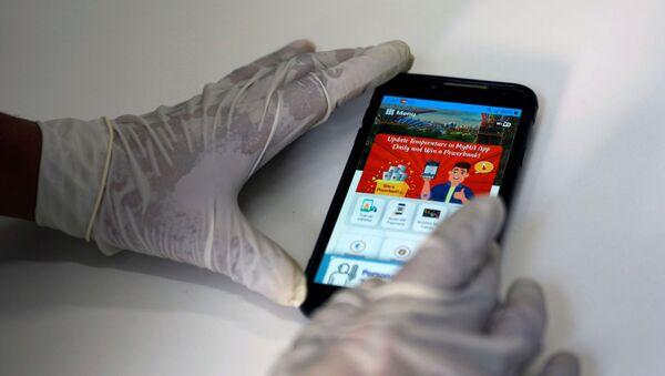 Un celular con una app del COVID-19 en la pantalla - Sputnik Mundo