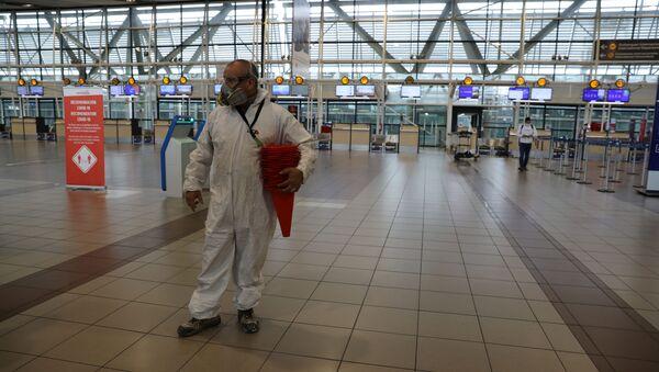 Una persona con traje protector en el aeropuerto de Santiago - Sputnik Mundo
