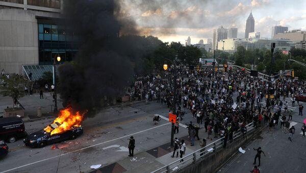 Un vehículo en llamas durante las protestas en Atlanta, Georgia, por la muerte de George Floyd - Sputnik Mundo