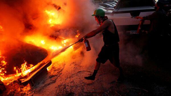 Un hombre trata de apagar el fuego en un vehículo durante una protesta en Minneapolis por la muerte de George Floyd - Sputnik Mundo