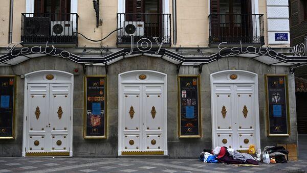 Una persona sin hogar duerme en una calle céntrica de Madrid el pasado mes de marzo. - Sputnik Mundo