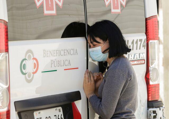 Mujer con mascarilla junta a ambulancia