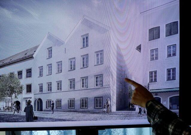Un hombre apunta a una pantalla de televisión que muestra el plan elegido para un rediseño arquitectónico de la casa en la que nació Adolf Hitler.
