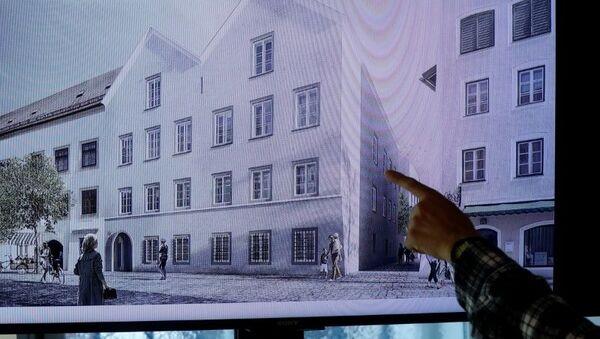 Un hombre apunta a una pantalla de televisión que muestra el plan elegido para un rediseño arquitectónico de la casa en la que nació Adolf Hitler. - Sputnik Mundo