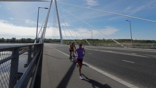 Un corredor y un ciclista (imagen referencial) - Sputnik Mundo
