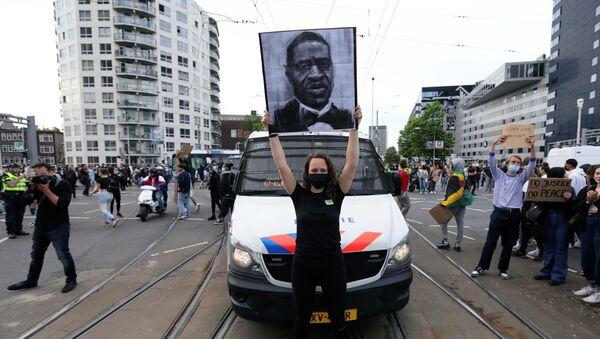Una manifestante con el retrato de George Floyd en las protestas antirascistas en EEUU - Sputnik Mundo