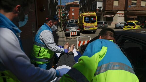 Médicos transportan a un paciente con coronavirus en España - Sputnik Mundo