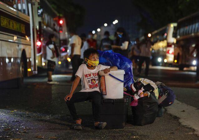 Un chico esperando el bus en Manila, Filipinas