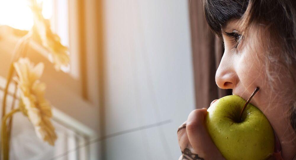 Niña mordiendo una manzana