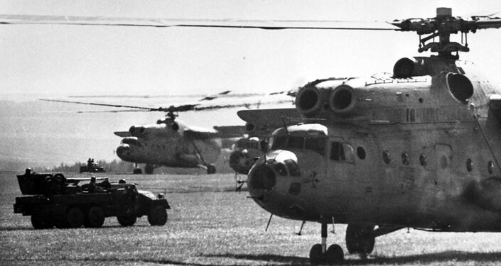 Dos helicópteros soviéticos Mi-6 sobre un campo.