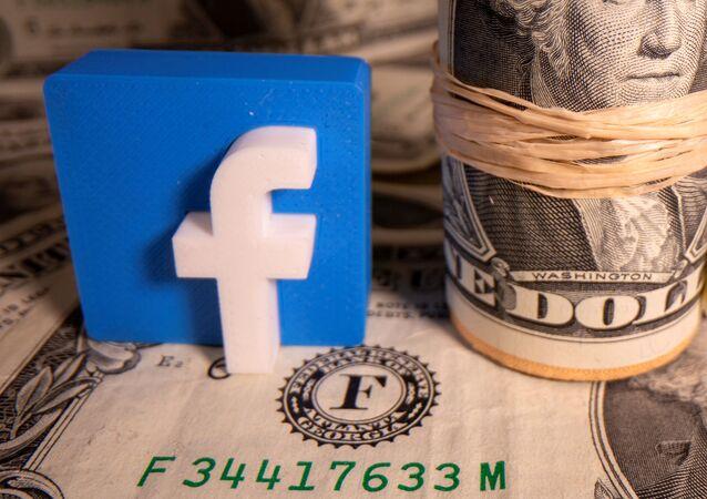 Un logo de la red social Facebook y un fajo de dólares estadounidenses
