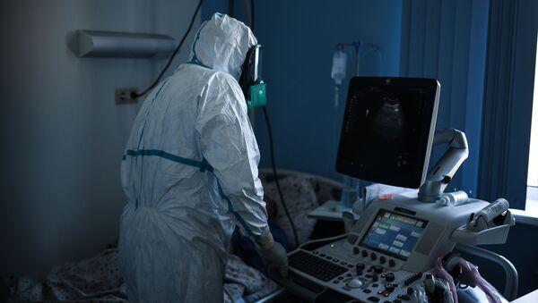 El personal médico lleva un traje protector en un hospital ruso para pacientes con COVID-19 - Sputnik Mundo