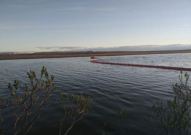 Rescatistas trabajan en el lugar de una fuga de combustible en el río después de un accidente en una central de energía en las afueras de Norilsk