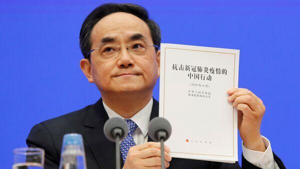 Xu Lin, vicepresidente del Departamento de Publicidad del Partido Comunista chino sostiene el libro blanco sobre COVID-19 - Sputnik Mundo