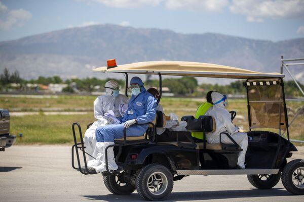 Médicos haitianos en el aeropuerto de Puerto Príncipe se retiran tras realizar controles médicos a haitianos deportados desde EEUU, en mayo de 2020. Desde el comienzo de la pandemia en marzo de 2020, Haití registra más de 19.170 casos positivos y 467 muertes confirmadas causadas por el SARS-CoV-2. - Sputnik Mundo